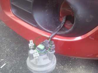 На фото – открученная ПТФ. Зеленым отмечен цоколь, которые предстоит разъединить для доступа к лампе