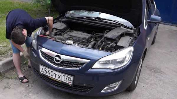 На фото: замена лампы ближнего света Opel Astra J может производиться даже на улице, главное – чтобы не шел дождь, так как влага губительно действует на все электрооборудование