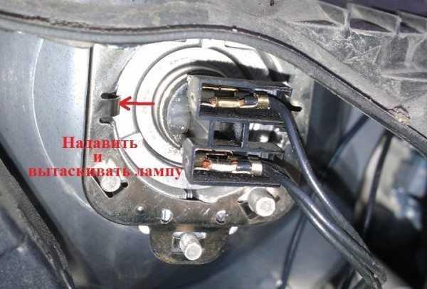 На фотографии показан фиксатор, который держит лампу и на который нужно нажать при ее снятии
