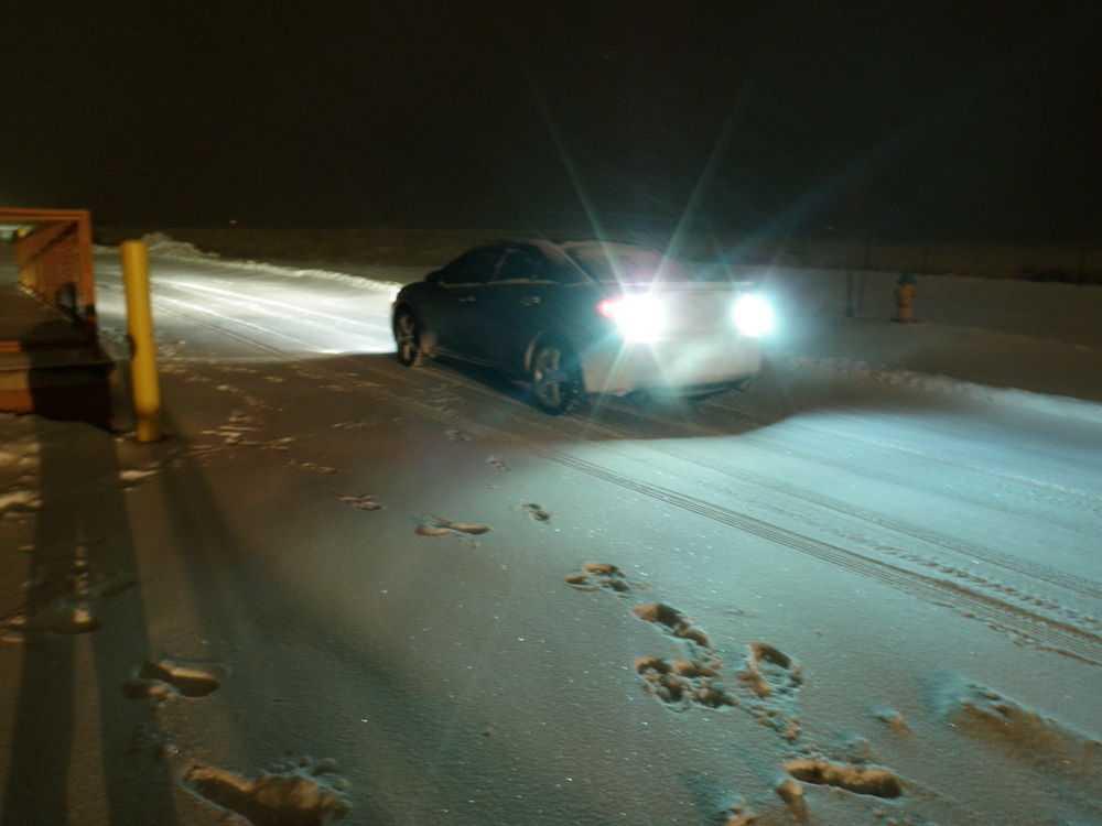 Автомобиль едет задним ходом ночью зимой по снегу