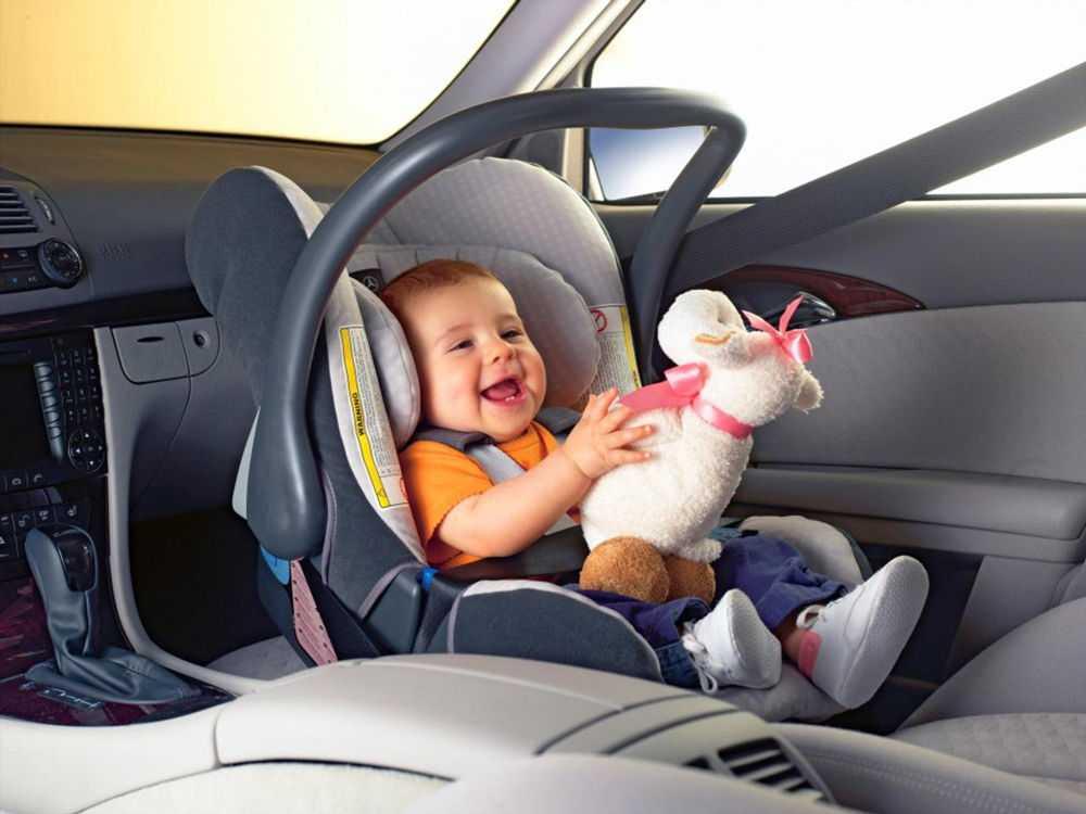 Ребенок с мягкой игрушкой в детском автокресле на переднем сидении