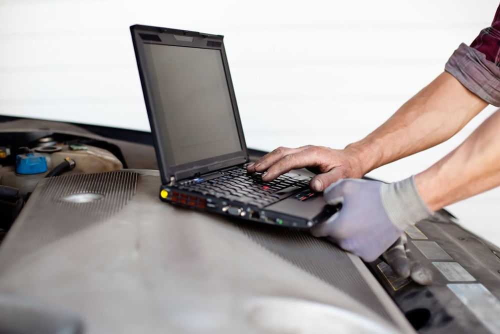 Мужчина чипует двигатель с помощью ноутбука