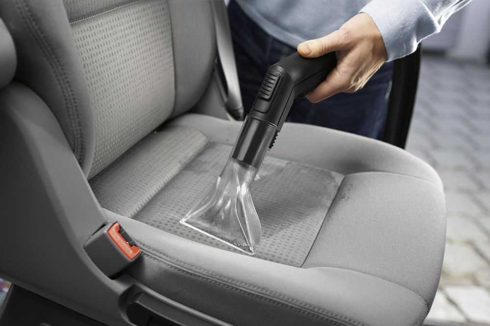 Человек моет сидения автомобиля моющим пылесосом