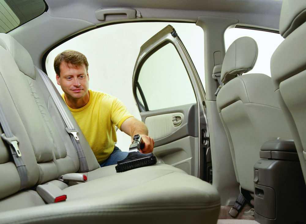 Мужчина пылесосит автомобиль