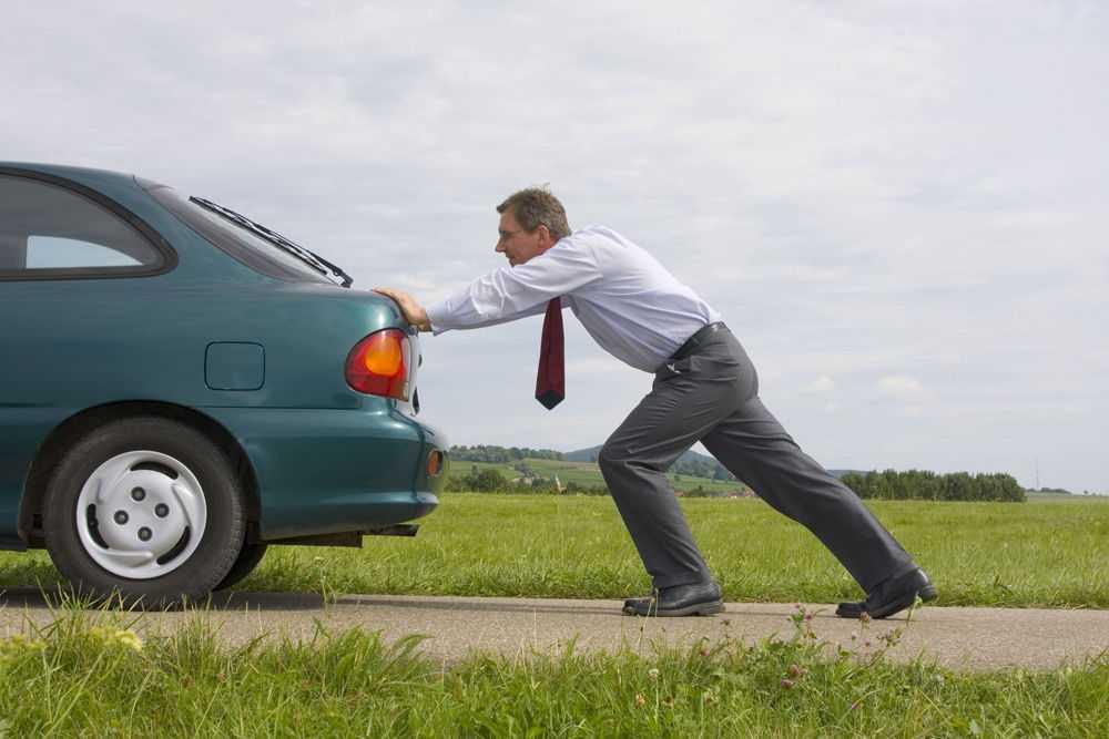 Мужчина с галстуком толкает автомобиль