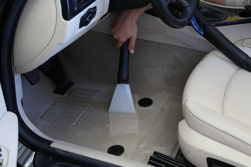 Человек чистит пол автомобиля