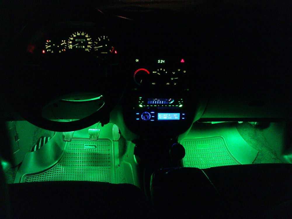Салон автомобиля с зеленой подсветкой ног