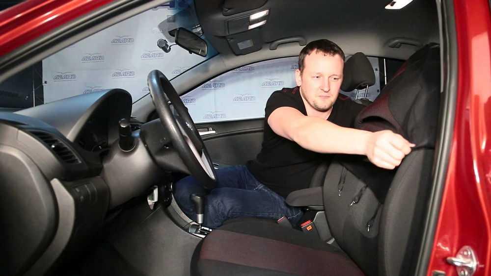 Мужчина устанавливает автомобильные чехлы