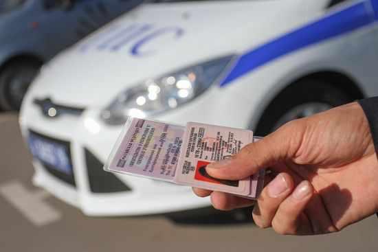 водительское удостоверение в руках инспектора ДПС