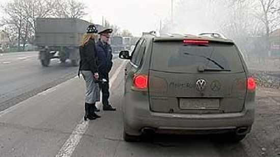 Инспектор ГИБДД выписывает девушке штраф за нечитаемый номер_